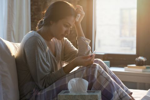 hispanic woman holding tissue reading pregnancy test