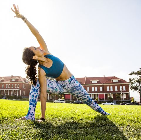 Hispanic woman practicing yoga in urban park