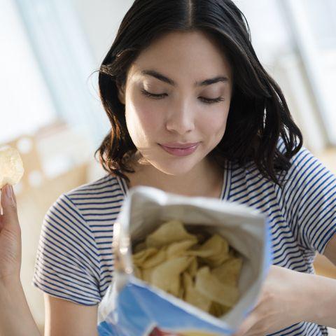 hispanic woman reading ingredients on bag of potato chips