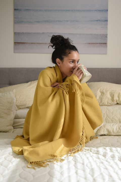 Hispanic woman sitting on bed wrapped in blanket drinking coffee