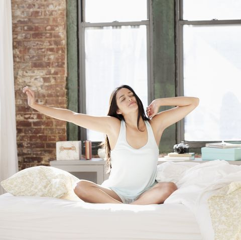 hispanic woman waking in morning and stretching arms