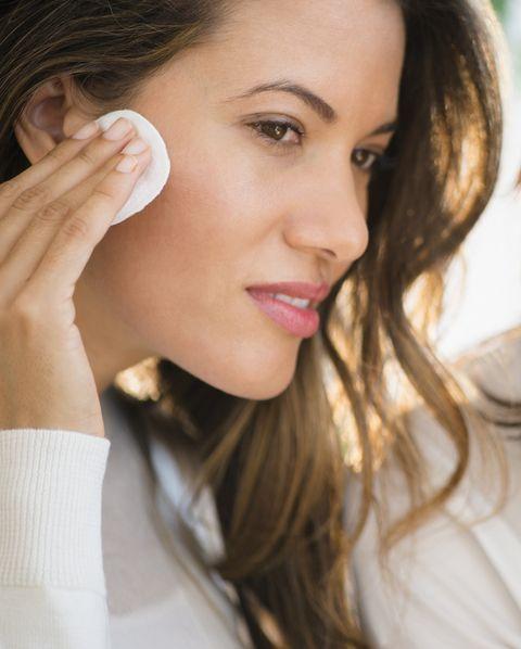hispanic women applying makeup in mirror