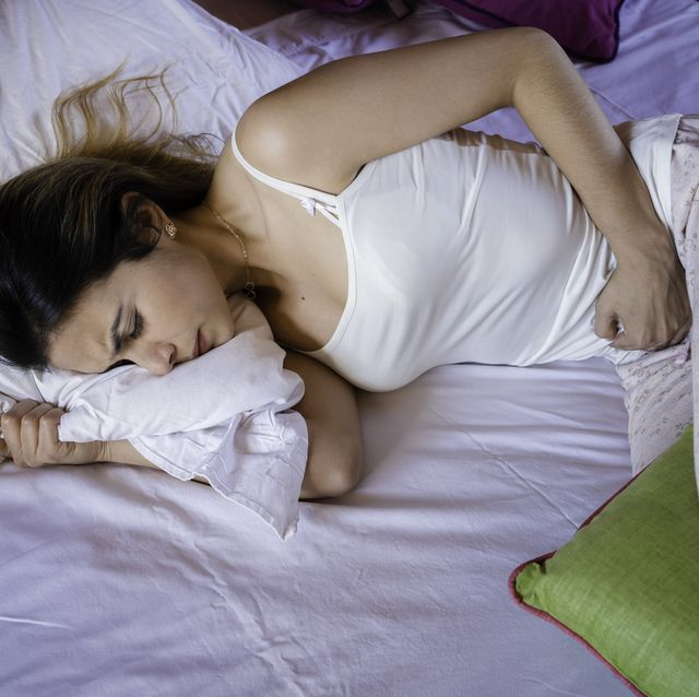 Hispanic young woman suffering PMS pain in bed