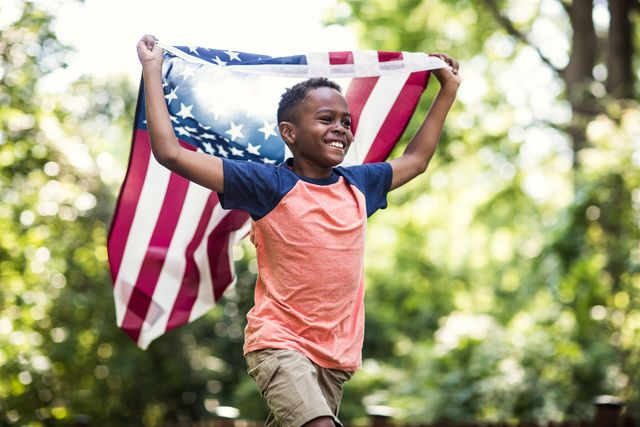 young boy running with american flag