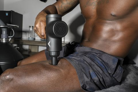 a massage gun is running along a man's thigh, creating a pulsating effect on his thigh as it relaxes his muscles