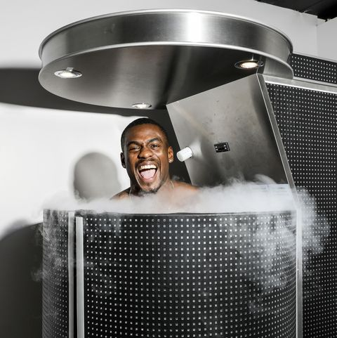 this is a man standing, smiling excitedly, in a cryotherapy unit, with cold air blowing out of it the unit itself is black and silver
