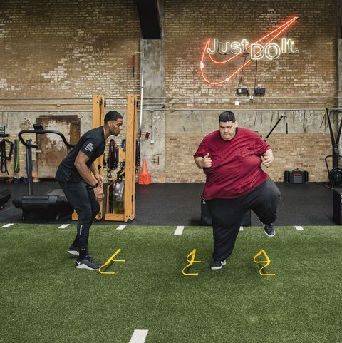 large man in gym working out with trainer on astroturf