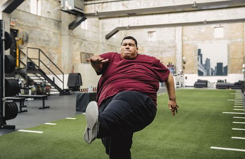 large man working out in gym with trainer