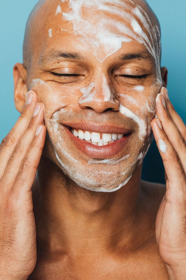 close up of black man smiling with cleansing scrub suds on his face