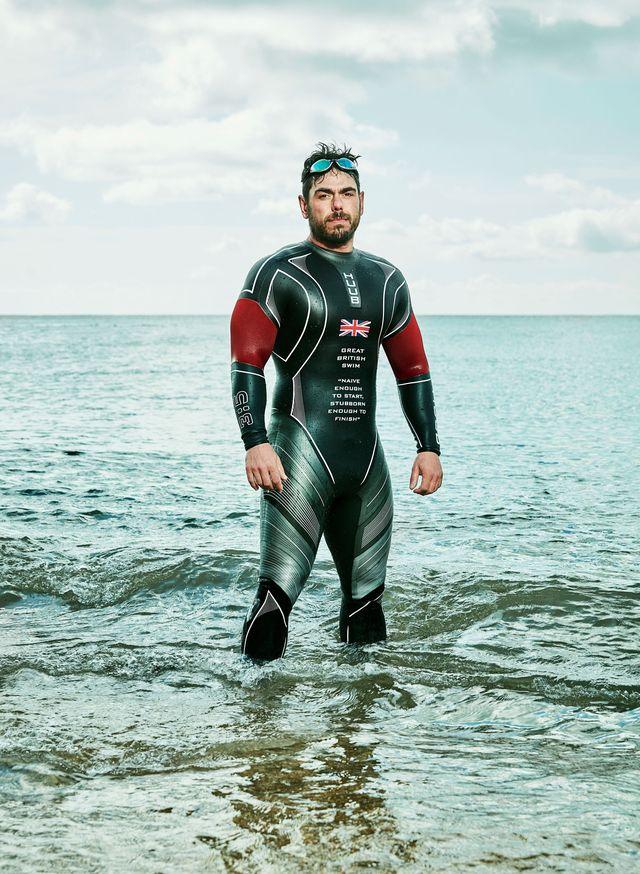 ross edgley in his wetsuit knee deep in the ocean