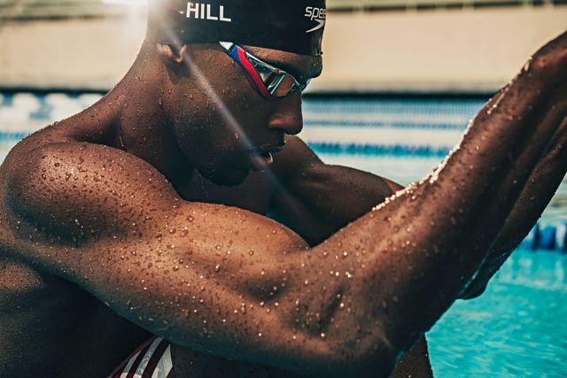 swimmer jamal hill preparing for a backstroke start holding self up on blocks