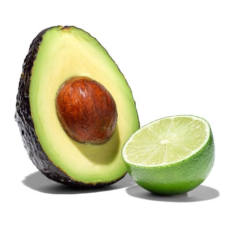 avocado half with pit and lime