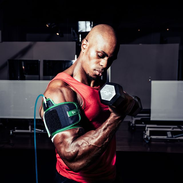 james mcmillan does a biceps curl while arm is in a blood flow restriction strap