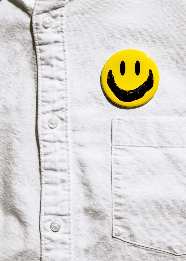 man's shirt with smiley face button on it