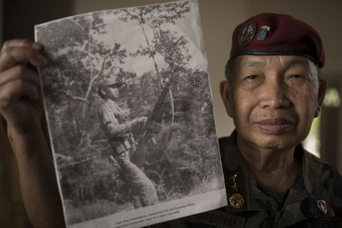Khao Insixiengmay held a photo of himself when he was 24 years old Wednesday at his home in July 5, 2017 in  Brooklyn Park, MN. Col. Insixiengmay is a veteran of the CIA's secret army in Laos during the Vietnam War. He's leading the effort of Lao Army vet