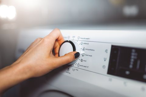 vrouw draait aan de knop van de wasmachine