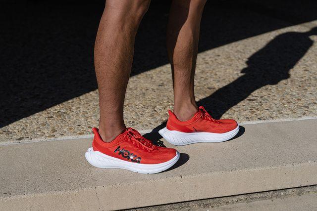 piernas de corredor con las zapatillas de running de hoka one one en color rojo y blanco