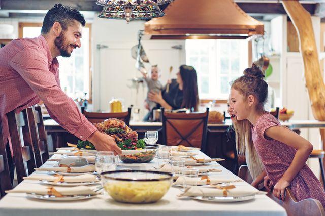 un padre presenta la comida de navidad en la mesa ante la mirada ilusionada de sus hijas