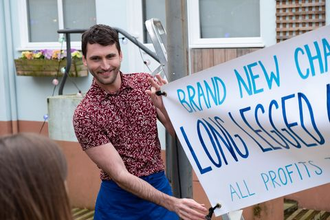 Damon Kinsella shows off a banner in Hollyoaks