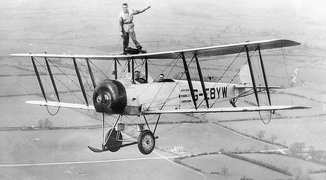 un hombre pilota un avión desde su parte superior en el año 1910
