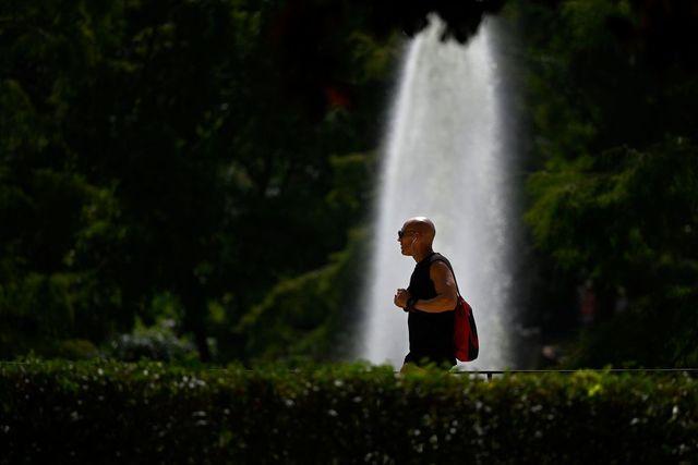 un hombre camina por un parque de madrid