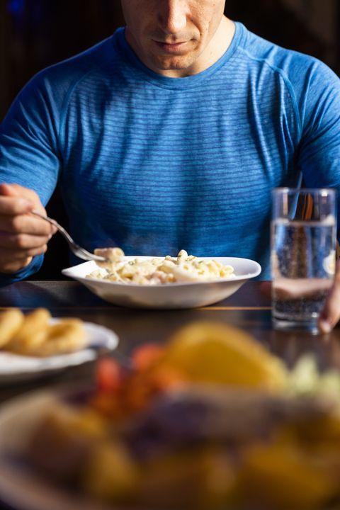un hombre comiendo pasta junto a una vaso de agua
