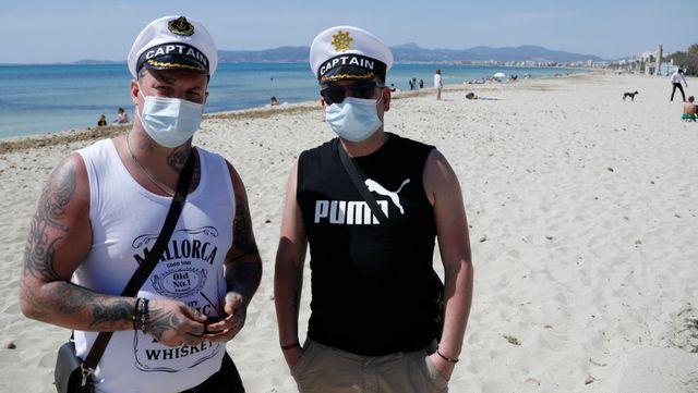 dos hombres posan en la pandemia de coronavirus tras tomar el sol en palma de mallorca