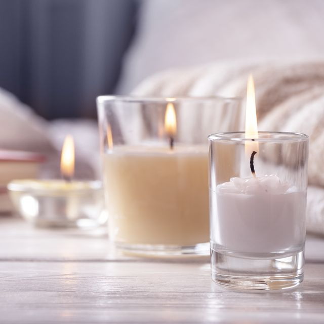 home interior still life with detailes several candles on white wooden table in front of bed, the concept of cosiness