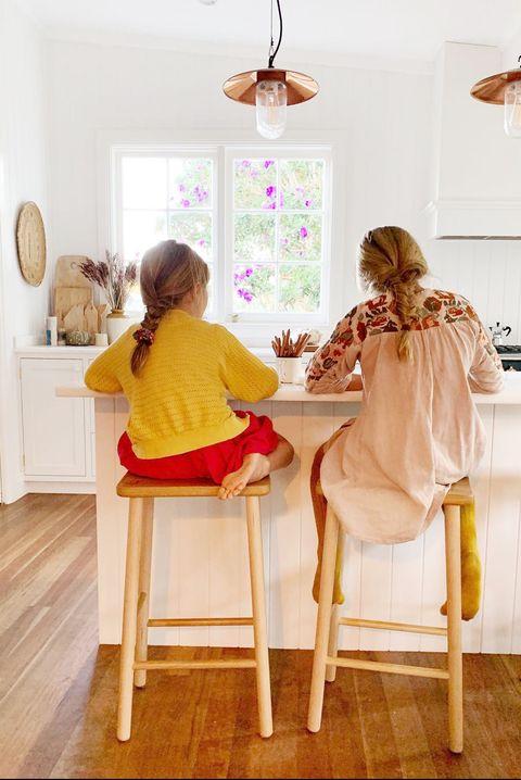 two girls doing homework at kitchen island