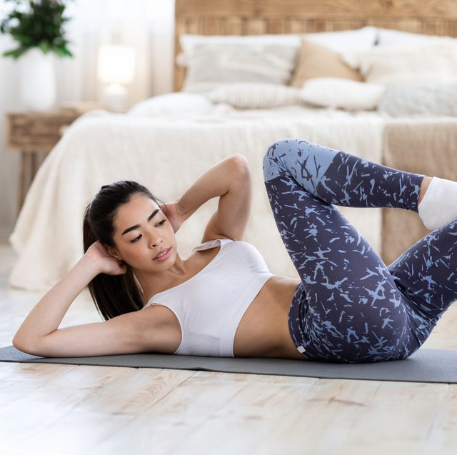Home Training. Fit asian girl doing abs workout in living room