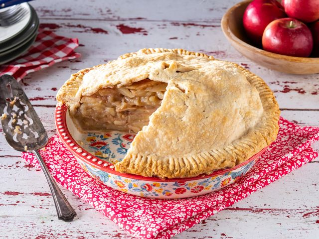 homemade apple pie in pie plate with bowl of apples in back
