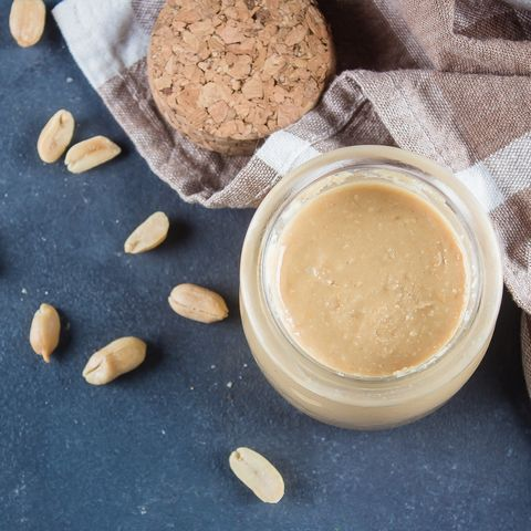 Homemade Peanut butter in glass jar and peanuts on blue concrete table background. Top view