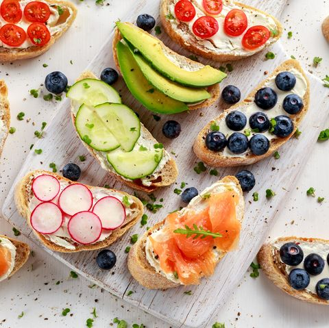 Homemade summer toast with cream cheese Smoked Salmon, Blueberries, Radish, Cucumber, Avocado and cress salad. Fresh healthy concept food.