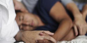 Homosexual couple lying in bed holding hands, sleeping
