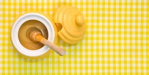 Manuka Honey pot and dipper on yellow background with copy space.