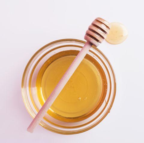 Honey spoon over glass bowl