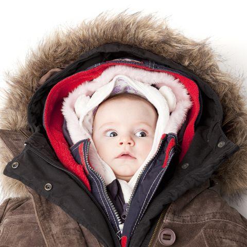 Hooded baby. Little girl in many winter jackets.