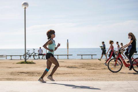 una mujer corre por un paseo marítimo de españa y se cruza con alguien que sale en bicicleta respetando los horarios establecidos para salir a hacer deporte en la fase 2 del confinamiento
