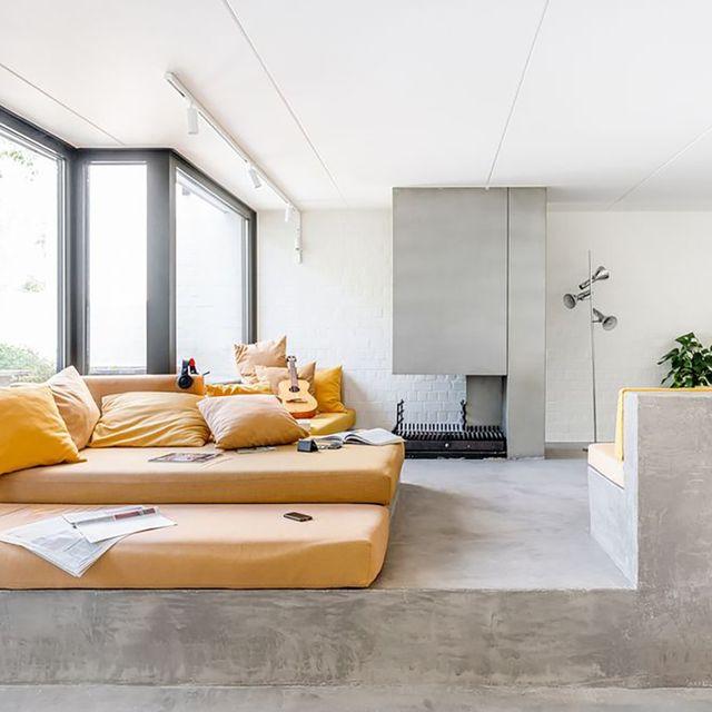 salón en cemento pulido, con textiles en color mostaza