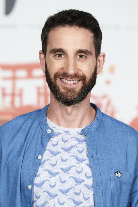 el actor y humorista dani rovira posando sonriendo en un photocall con camisa azul