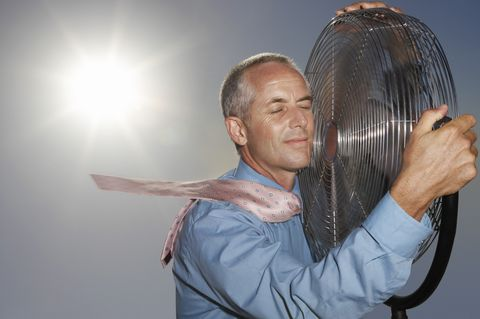 Hot, Relieved Businessman Holding an Electric Fan