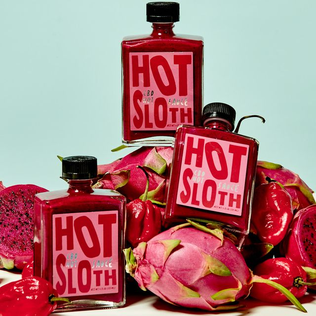 hot sloth bottles stacked on dragon fruit and peppers