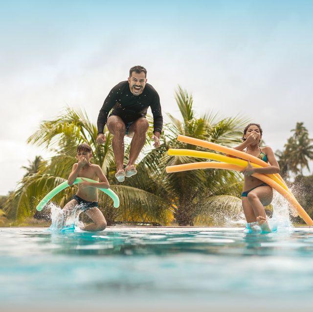 padre saltando con dos niños a una piscina