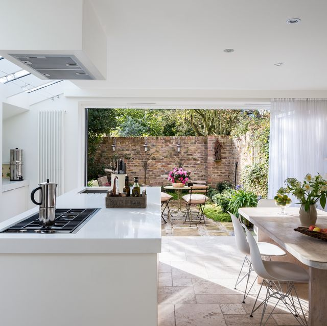 open plan white modern kitchen with custom made table of lime and oak and plastic eames chairs