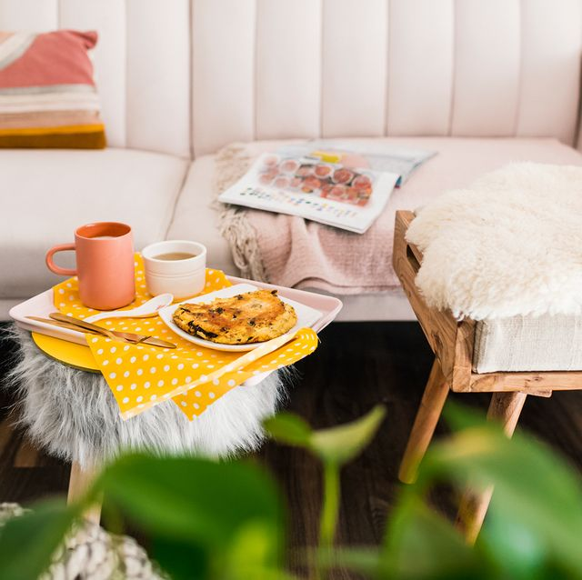 living room with pink velvet couch and coffee on fur ottoman