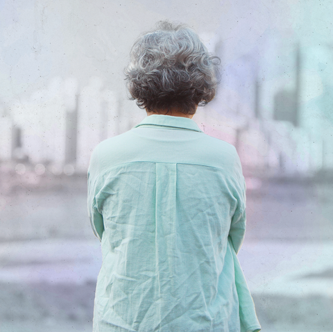 an older woman standing outside looking at a city skyline