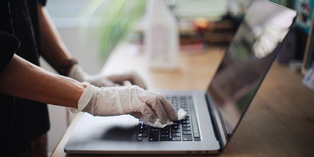 woman is sanitising her laptop surface agains viruses and germs in midst of the coronavirus   covid19 worldwide outbreak