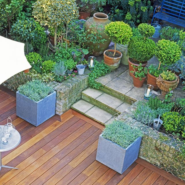 aerial view of a stylish town garden with wooden decking area, two metal square flower containers of lavender, sun umbrella, cafe table and chair