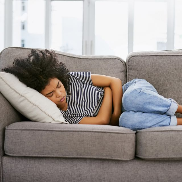 Woman lying on couch with arms wrapped around midsection.