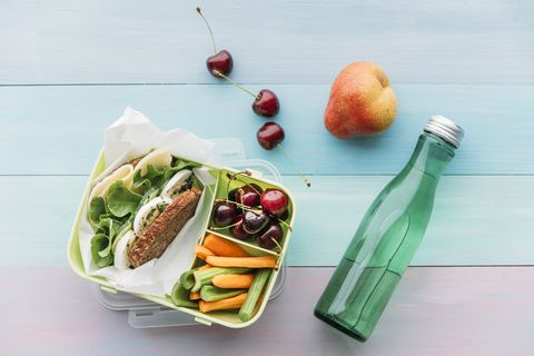 Lunch box with sandwich, cherries, carrots, and celery next to bottle of water.